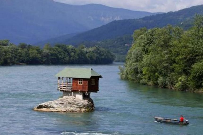 A man powers a boat near a house built on a rock on the river Drina near the western Serbian town of Bajina Basta, about 160km from the capital Belgrade on May 22, 2013. The house was built in 1968 by a group of young men who decided that the rock on