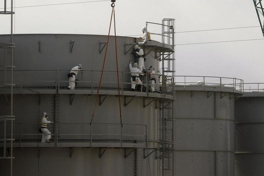 Workers wearing protective suits and masks constructing water tanks is seen through a bus window at Tokyo Electric Power Co. (Tepco)'s tsunami-crippled Fukushima Daiichi nuclear power plant in Fukushima prefecture in this Feb 20, 2012 file photo. The