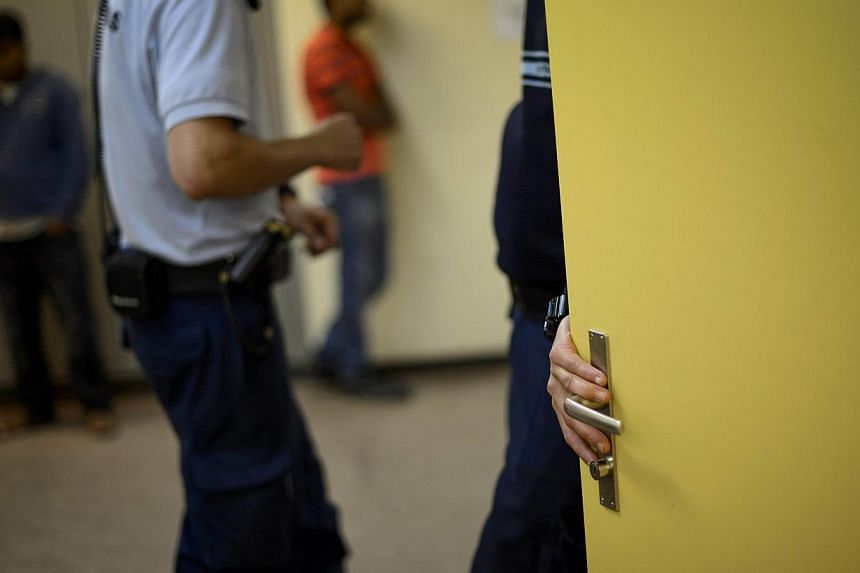A private guard speaking with his colleague holds a door next to asylum seekers on Aug 9, 2013 in a military bunker in remote Alpine village of Realp, Central Switzerland during a press visit by Swiss Federal Migration Office at a temporary asylum ce