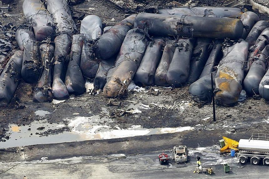 A firefighter stands close to the remains of a train wreckage in Lac Megantic in this file photo taken on July 8, 2013. -- FILE PHOTO: REUTERS