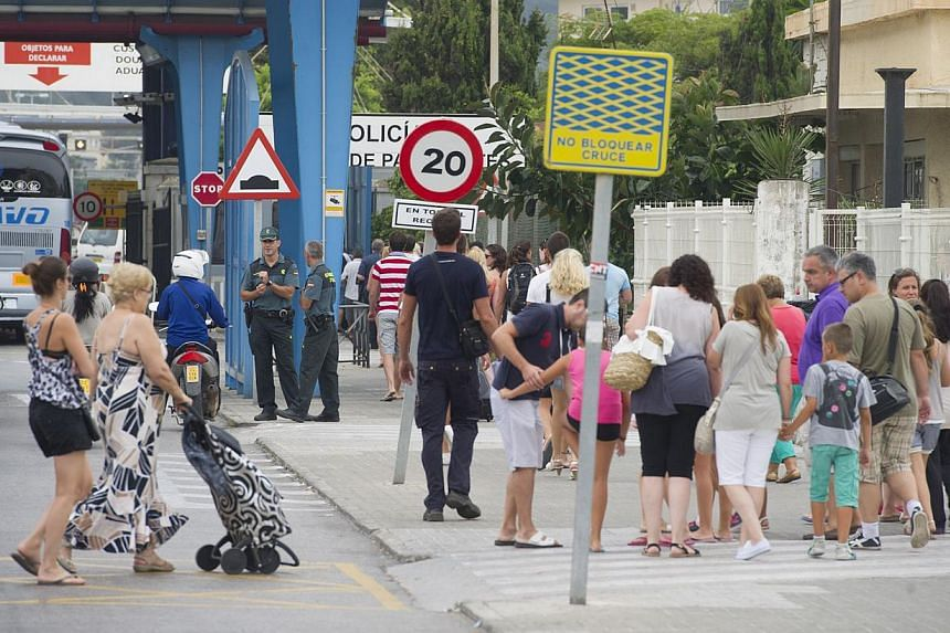 Motorists queue as pedestrians walk on Aug 13, 2013 at the border crossing between Spain and Gibraltar in La Linea de la Concepcion. Irate drivers waited up to five hours to enter Gibraltar today, some even pushing their cars to save fuel, as Spain e