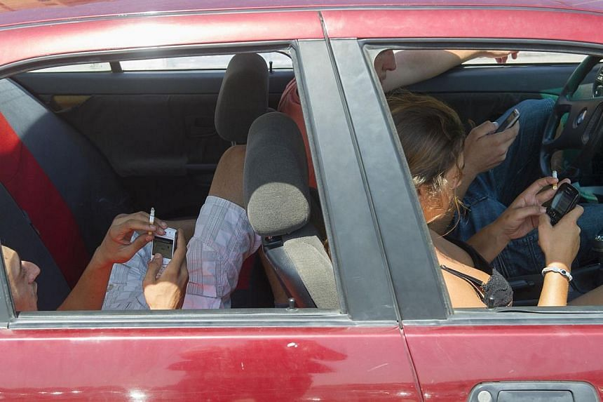 Passengers smoke and use their mobile phones as they queue on Aug 13, 2013 at the border crossing between Spain and Gibraltar in La Linea de la Concepcion. -- PHOTO: AFP