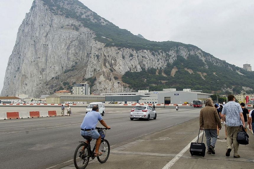 People cross the Gibraltar airport tarmac after the border crossing between Spain and Gibraltar on Aug 13, 2013. Irate drivers waited up to five hours to enter Gibraltar today, some even pushing their cars to save fuel, as Spain enforced tight border