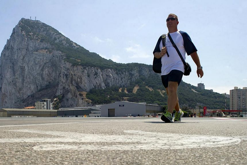 A man crosses the Gibraltar airport tarmac before the border crossing between Spain and Gibraltar on Aug 13, 2013. Irate drivers waited up to five hours to enter Gibraltar today, some even pushing their cars to save fuel, as Spain enforced tight bord