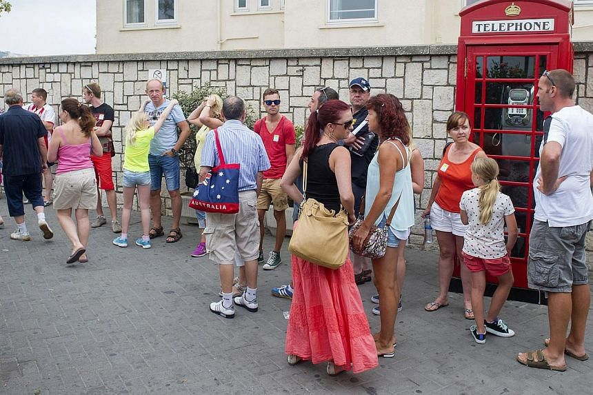 Tourists wait for taxis near a phone booth in Gibraltar on Aug 13, 2013. This rock of seven square kilometers enclosed in the coast of Andalusia, off the tip of southern Spain, is reminiscent of England: the red phone booths, mailboxes Royal Mail, th