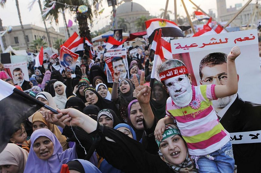Supporters of Egypt's ousted President Mohammed Morsi wave his posters and national flags as one carries her daughter with a mask of him during a protest in Nahda Square, where protesters have installed their camp near Cairo University in Giza, south