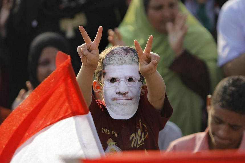 A Supporter of Egypt's ousted President Mohammed Morsi flashes victory signs as he puts on a mask with his picture during a protest in Nahda Square, where protesters have installed their camp near Cairo University in Giza, in south-western of Cairo,