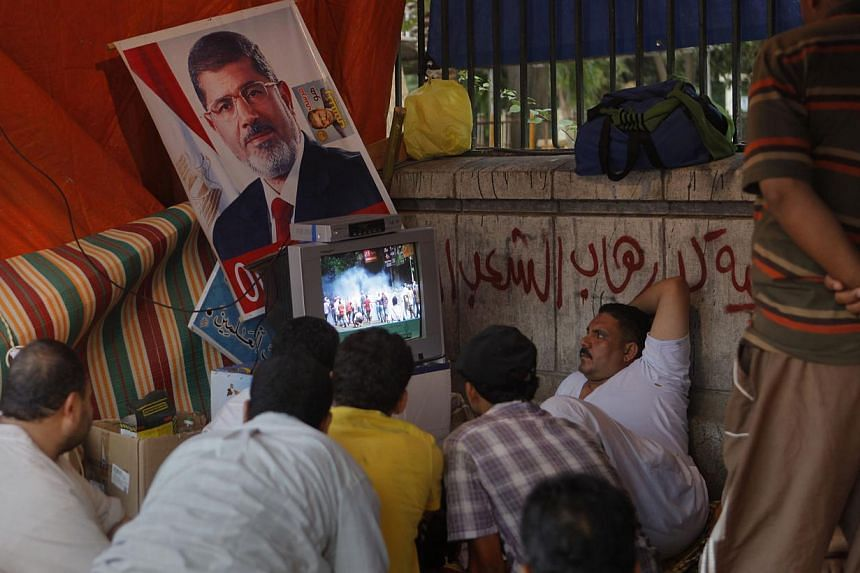 Supporters of Egypt's ousted President Mohammed Morsi watch the news at their tent in Nahda Square, where protesters have installed their camp near Cairo University in Giza, south-western Cairo, Egypt, on Tuesday, Aug 13, 2013. -- PHOTO: AP
