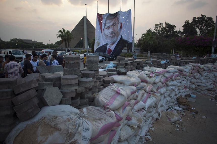 Supporters of Egypt's ousted President Mohammed Morsi stand behind sand barriers recently set up where supporters of Morsi have installed a camp and held daily rallies outside Rabaah al-Adawiya mosque in Cairo, Egypt, on Tuesday, Aug 13, 2013. -- PHO