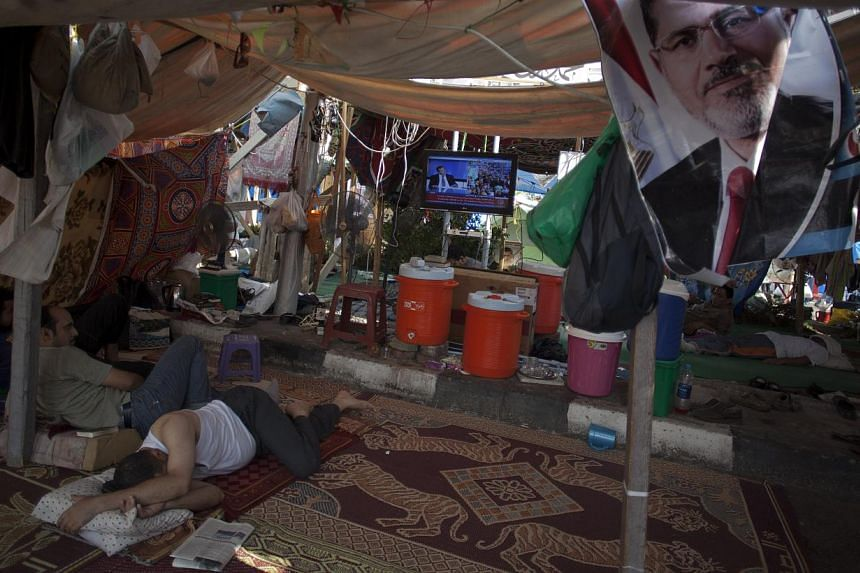 Supporters of Egypt's ousted President Mohammed Morsi rest in a tent watching TV outside Rabaah al-Adawiya mosque, where protesters have installed a camp and held daily rallies at Nasr City, Cairo, Egypt, on Tuesday, Aug 13, 2013. -- PHOTO: AP