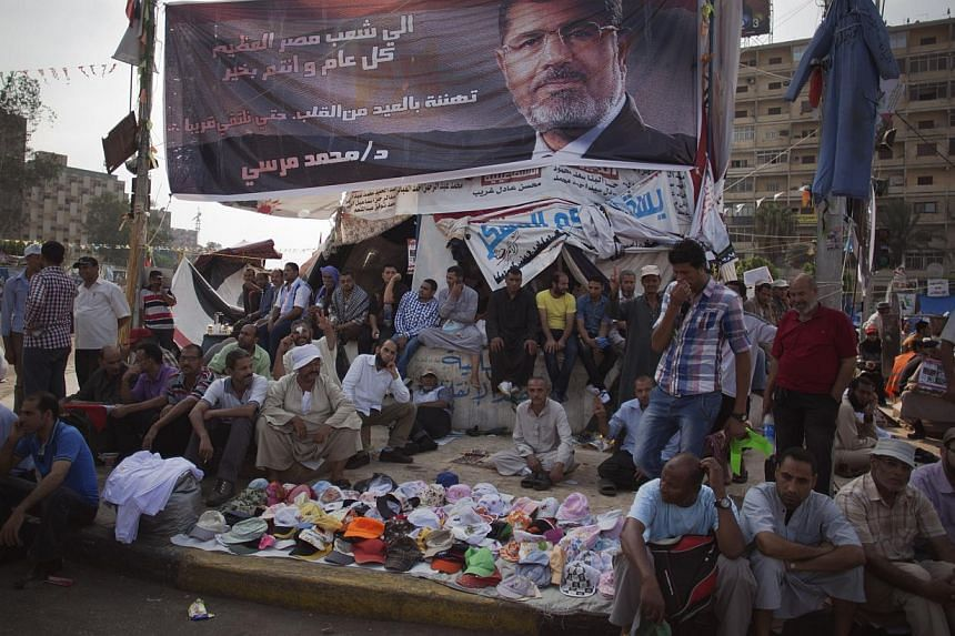 "Supporters of Egypt's ousted President Mohammed Mursi sit under a banner of Mr Mursi with Arabic writing that reads ""To the great Egyptian people, Happy year, Congrats on the Eid from the heart, Mohammed Mursi,"" outside Rabaah al-Adawiya mosque, wher"