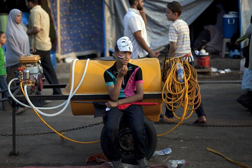 An Egyptian boy rests on a water tank outside Rabaah al-Adawiya mosque, where supporters of Egypt's ousted President Mohammed Morsi have installed a camp and held daily rallies at Nasr City, Cairo, Egypt, on Tuesday, Aug 13, 2013. -- PHOTO: AP