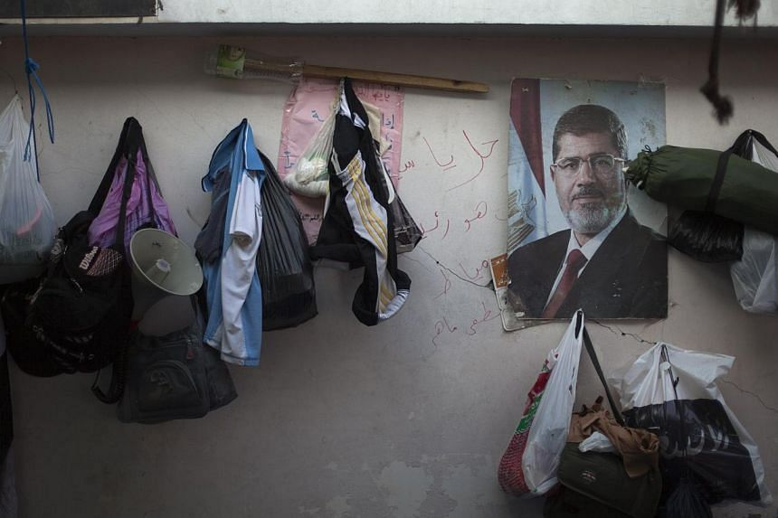 Clothes hang on a wall next to a poster of Egypt's ousted President Mohammed Morsi outside Rabaah al-Adawiya mosque, where protesters have installed a camp and held daily rallies at Nasr City, Cairo, Egypt, on Tuesday, Aug 13, 2013. -- PHOTO: AP
