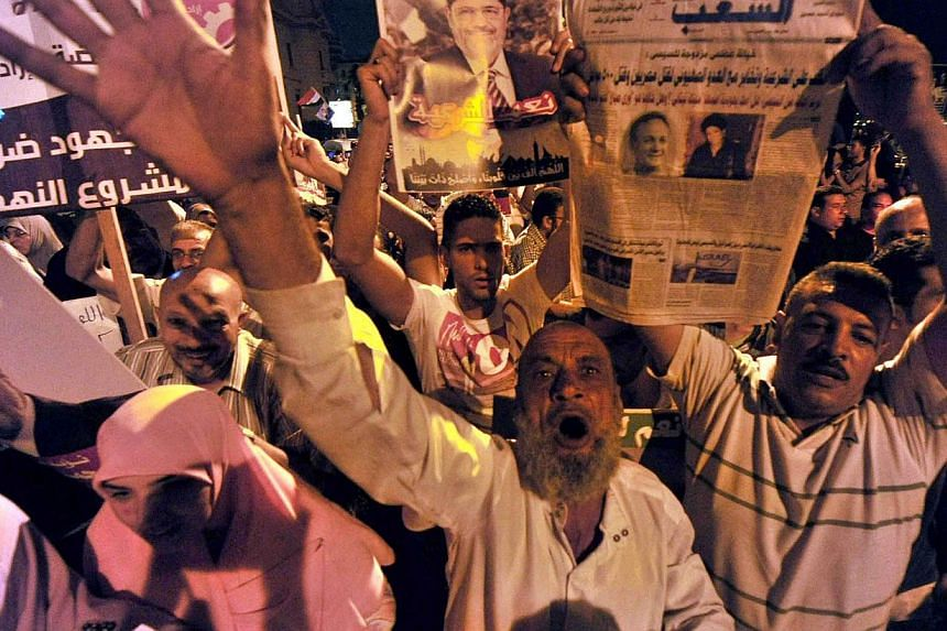 Muslim Brotherhood supporters shout slogans as they wave portraits of Egypt's ousted president Mohamed Morsi during a demonstration in the port city of Alexandria on Aug 13, 2013, against the former leader's overthrow by the military.  -- PHOTO: