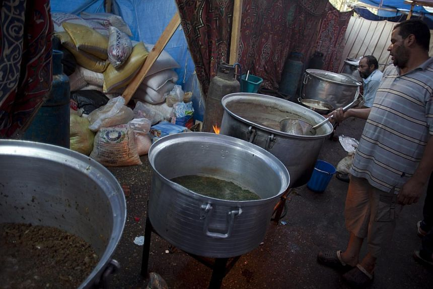 Supporters of Egypt's ousted President Mohammed Morsi prepare food to distribute to protesters outside Rabaah al-Adawiya mosque, where they have installed a camp and held daily rallies at Nasr City, Cairo, Egypt, on Tuesday, Aug 13, 2013. -- PHOTO: A