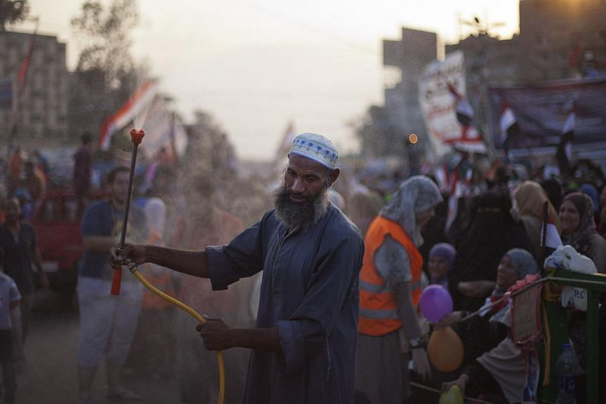 A Supporter of Egypt's ousted President Mohammed Morsi sprays water on protesters outside Rabaah al-Adawiya mosque, where they have installed a camp and held daily rallies at Nasr City, Cairo, Egypt, on Tuesday, Aug 13, 2013. -- PHOTO: AP