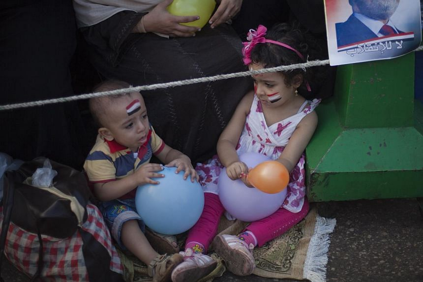 Two Egyptian children play with balloons as they sit next to a picture of Morsi outside Rabaah al-Adawiya mosque, where supporter of Egypt's ousted President Mohammed Morsi have installed a camp and held daily rallies at Nasr City, Cairo, Egypt, on T