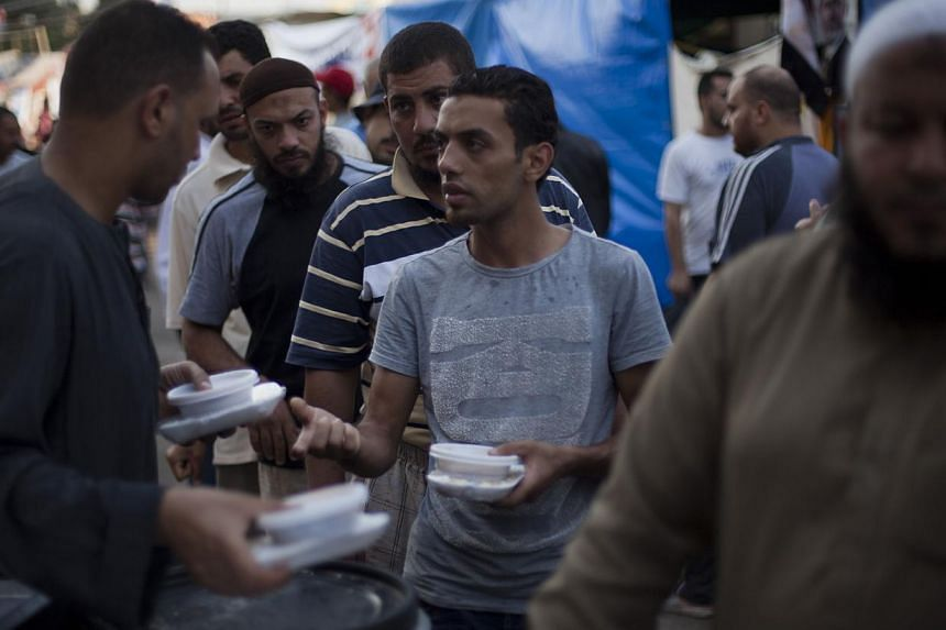 Supporters of Egypt's ousted President Mohammed Morsi distribute food in plastic dishes to protesters outside Rabaah al-Adawiya mosque, where they have installed a camp and held daily rallies at Nasr City, Cairo, Egypt, on Tuesday, Aug 13, 2013. -- P