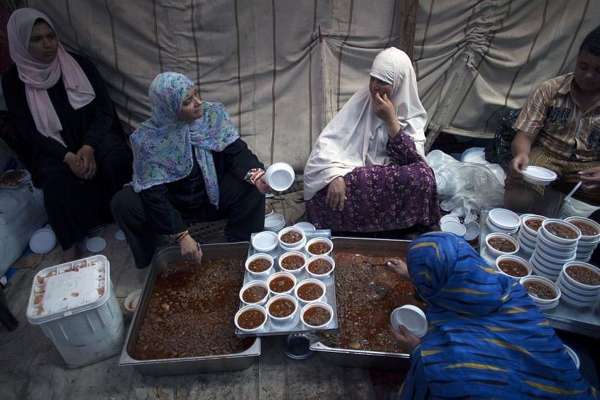 Supporters of Egypt's ousted President Mohammed Morsi serve food on plastic dishes to distribute to protesters outside Rabaah al-Adawiya mosque, where they have installed a camp and held daily rallies at Nasr City, Cairo, Egypt, on Tuesday, Aug 13, 2