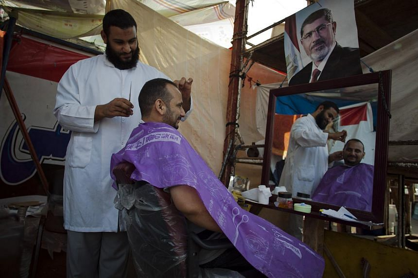 A supporter of Egypt's ousted President Mohammed Morsi gets his hair cut in a tent outside Rabaah al-Adawiya mosque, where protesters have installed a camp and held daily rallies at Nasr City, Cairo, Egypt, on Tuesday, Aug 13, 2013. -- PHOTO: AP