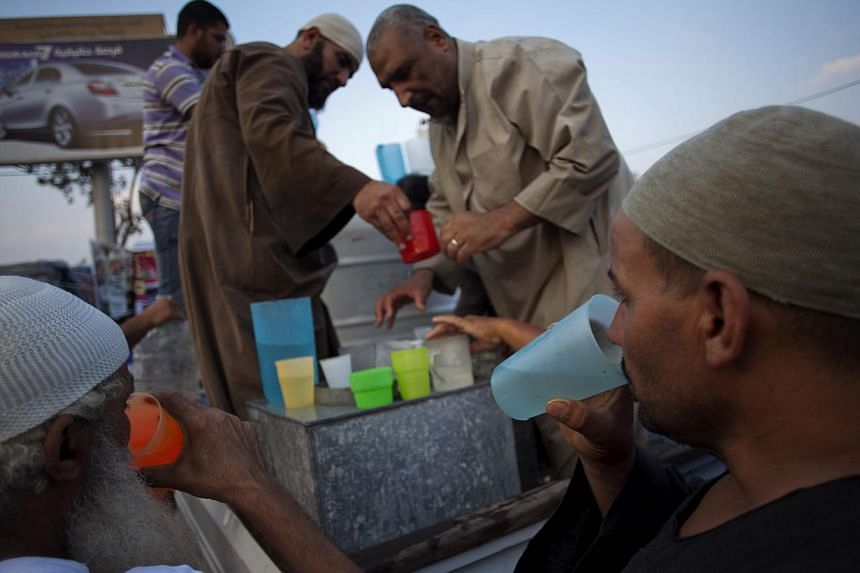 Supporters of Egypt's ousted President Mohammed Morsi distribute cold water to protesters outside Rabaah al-Adawiya mosque, where they have installed a camp and held daily rallies at Nasr City, Cairo, Egypt, on Tuesday, Aug 13, 2013. -- PHOTO: AP