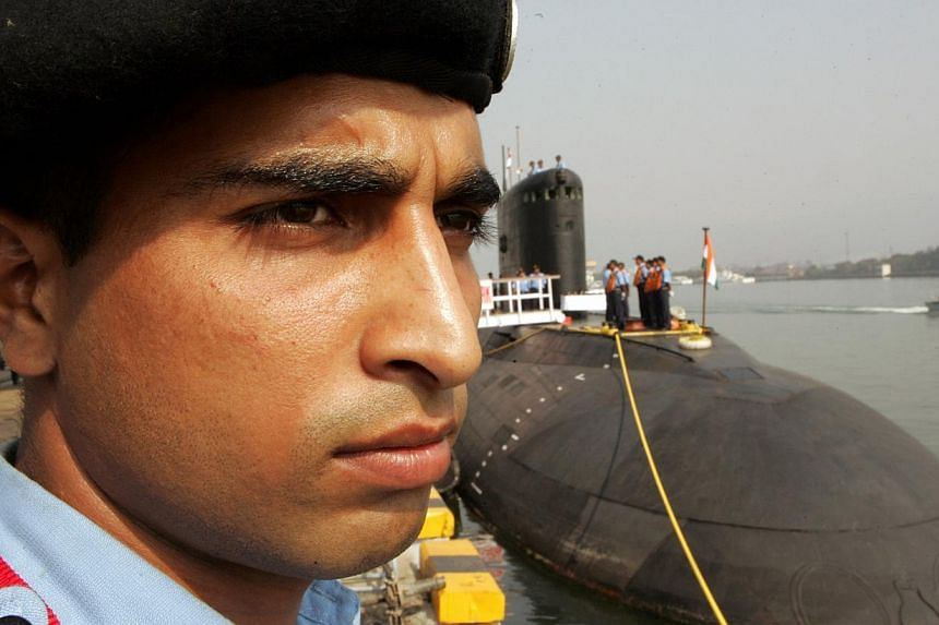 An Indian Navy security officer stands guard near a Sindhurakshak submarine ahead of Indian President Abdul Kalam's visit in Visakhapatnam in this Feb 13, 2006, photo. About 18 Indian sailors were trapped after an explosion and fire on board the Sind