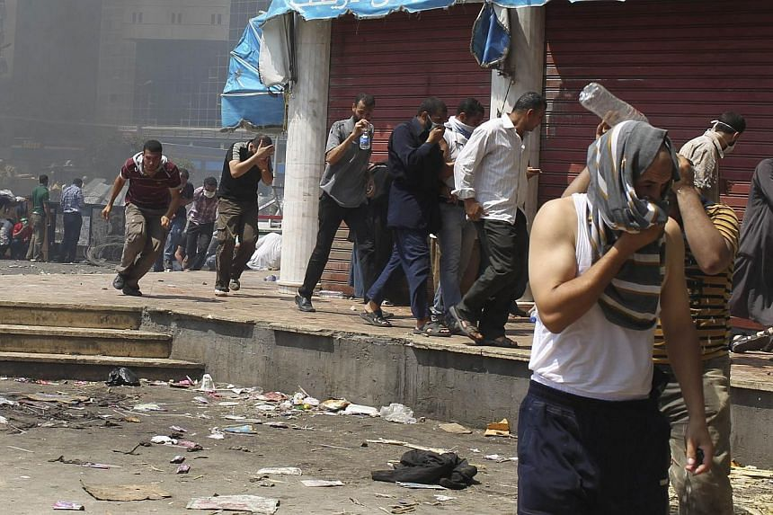 Members of the Muslim Brotherhood and supporters of ousted Egyptian President Mohamed Mursi flee from tear gas and rubber bullets fired by riot police and army personnel around the area of Rabaa Adawiya square, where they are camping, in Cairo, Aug 1