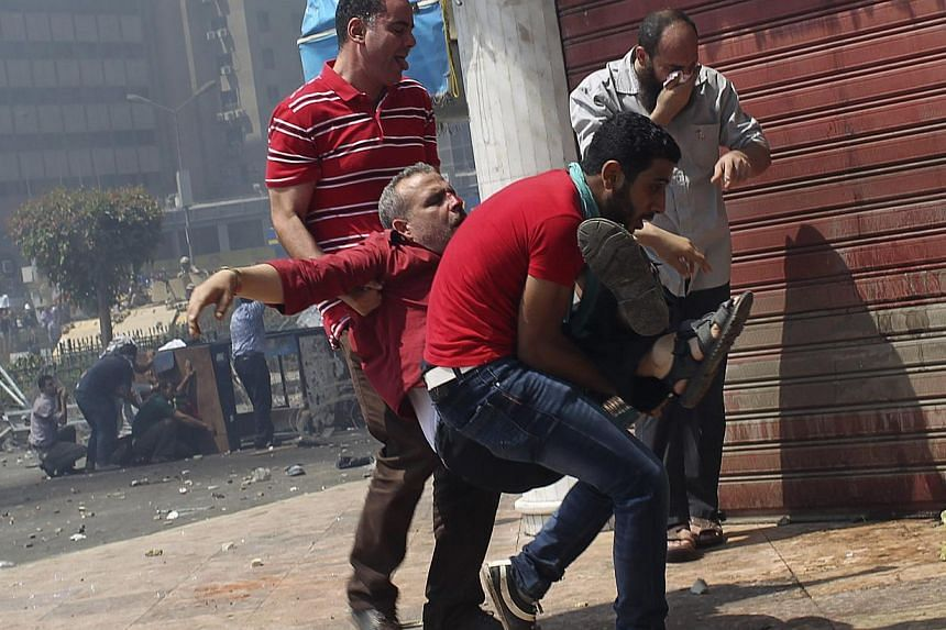 Supporters of deposed Egyptian President Mohamed Mursi carry a protester injured during clashes with riot police and army at around the area of Rabaa Adawiya square, where they are camping, in Cairo, Aug 14, 2013. -- PHOTO: REUTERS