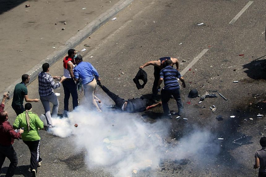 A member of the security forces is dragged and stripped of his vest by protesters after his police vehicle was pushed off the 6th of October bridge by protesters, near the largest sit-in by supporters of ousted Islamist President Mohammed Mursi in th