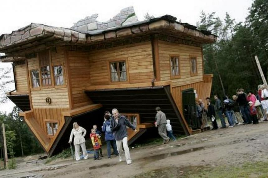 People wait in line to visit an upside-down house built at the Centre of Education and Promotion of the Region in the village of Szymbark, northern Poland on July 31, 2007. -- FILE PHOTO: REUTERS
