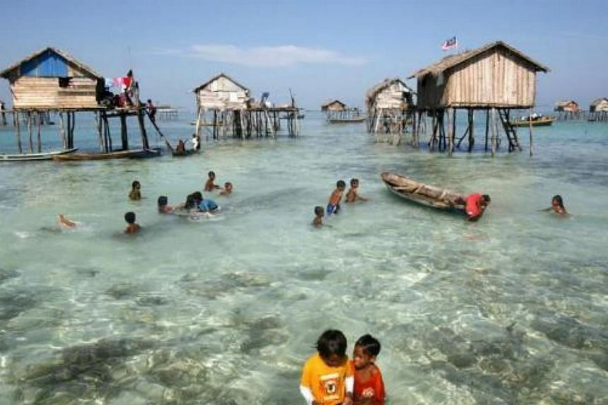 Young sea gypsies play in the water in the center of their neighborhood in the Sulawesi Sea in Malaysia's state of Sabah on the Borneo island on Feb 17, 2009. A community of 30 families of the indigenous ethnic group of sea gypsies are still maintain