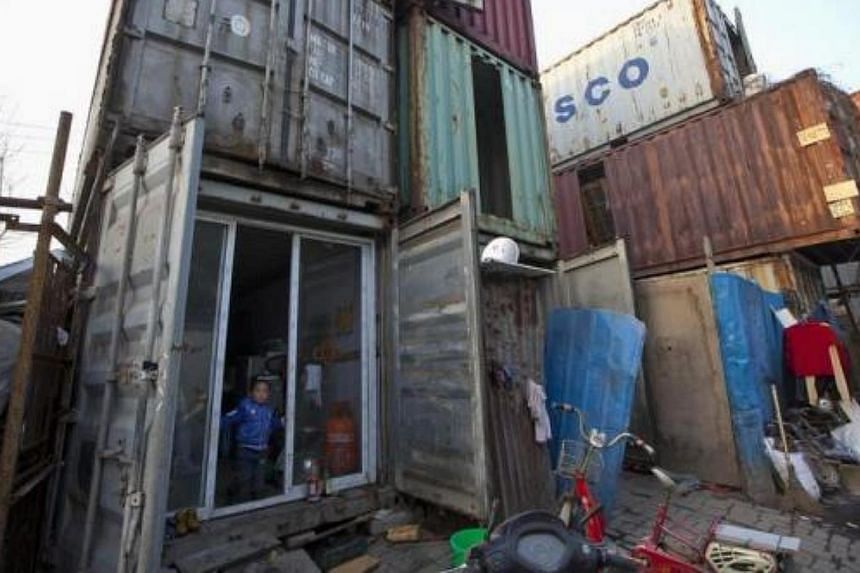 A child stands at the door of a shipping container serving as his accommodation, in Shanghai on Mar 4, 2013. The containers, which house different families, were set up by the landlord, who charges a rent of 500 yuan (S$103) per month for each contai