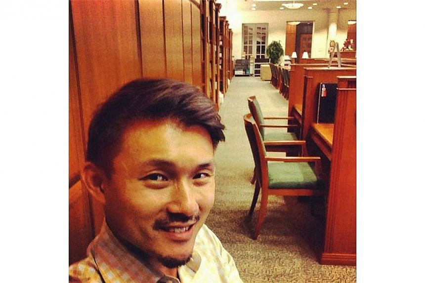 Mr Baey paused for a selfie while working at the Parliament library on Aug 5. -- PHOTO BY: BAEY YAM KENG