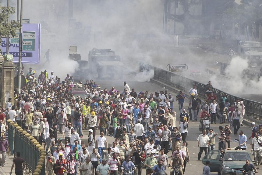 Riot police vehicles fire tear gas at members of the Muslim Brotherhood and supporters of deposed Egyptian President Mohamed Mursi on Wednesday, Aug 14, 2013. Turkey branded the deadly crackdown in Egypt on protesters loyal to ousted president Mohame