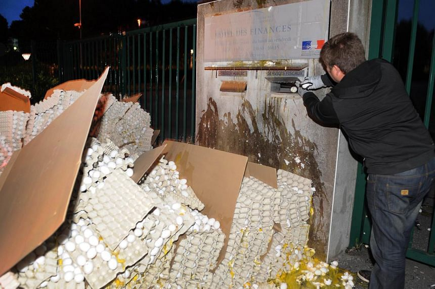 A French egg producer throws eggs in a mail box as he break eggs in front of the taxes and internal revenue service office in Carhaix-Plouguer, Brittany, western France, during a protest action, on August 7, 2013. French poultry farmers who last
