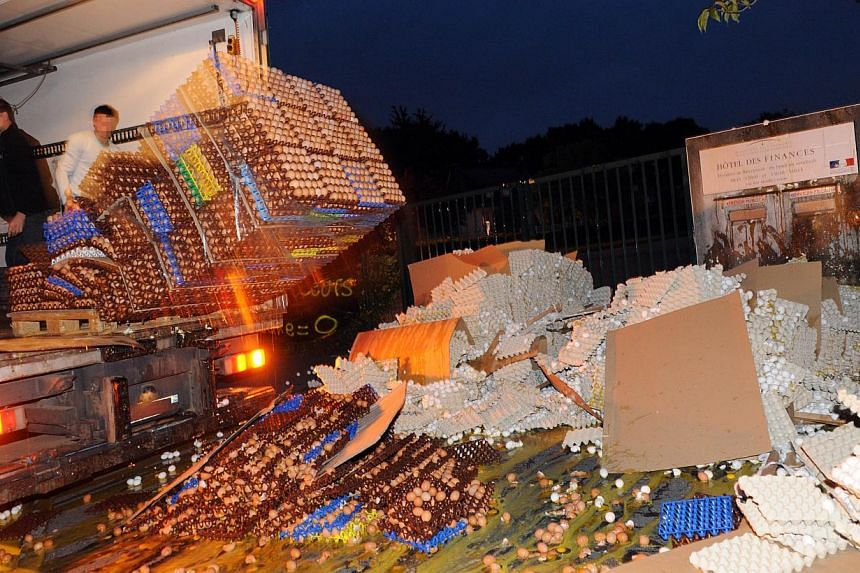 French egg producers throw crates of eggs from the back of a truck onto the sidewalk in front of the taxes and internal revenue service office in Carhaix-Plouguer, Brittany, western France, during a protest action, on August 7, 2013. French poul