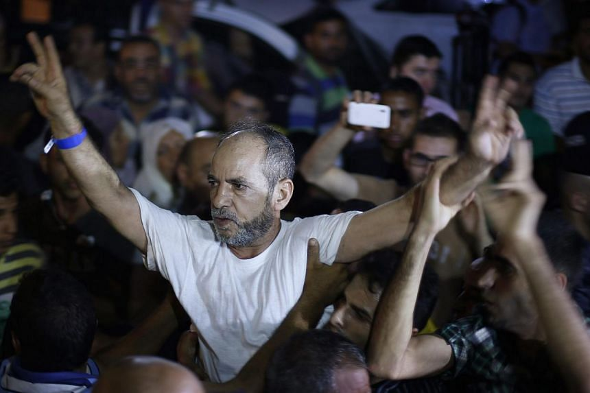 A freed Palestinian prisoner gestures upon his arrival near Erez crossing, between Israel and northern Gaza Strip, early Aug 14, 2013.Israel began an operation to free 26 Palestian prisoners on Tuesday hours before the two sides were to hold ne