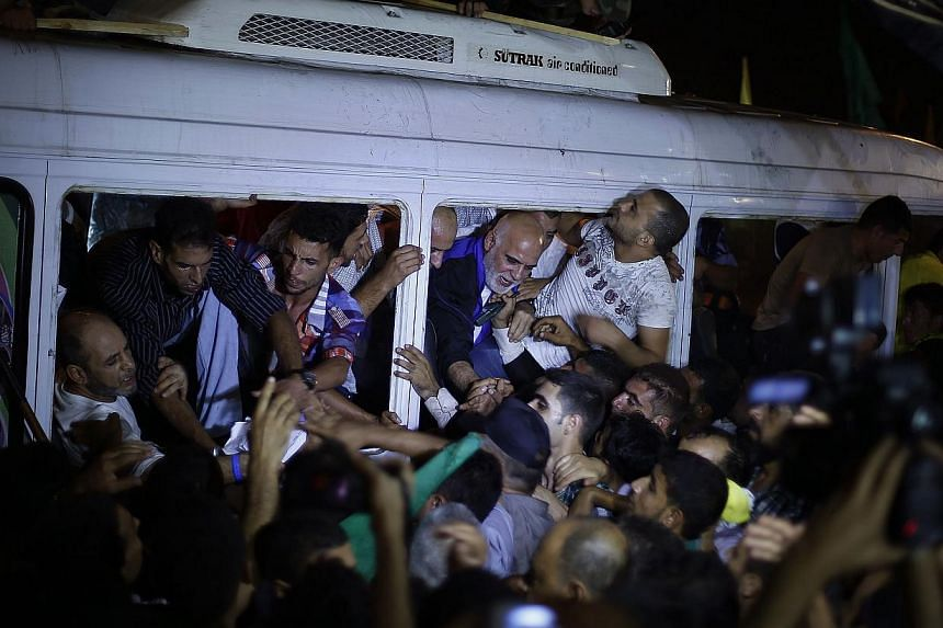 People greet freed Palestinian prisoners in a bus upon their arrival near Erez crossing, between Israel and northern Gaza Strip, early Aug 14, 2013. Israel began an operation to free 26 Palestian prisoners on Tuesday hours before the two sides w