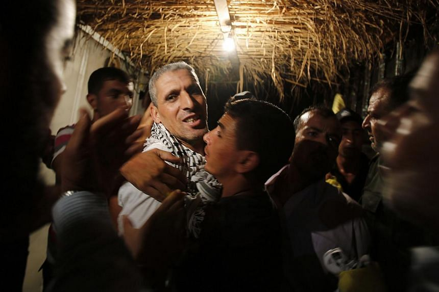 A freed Palestinian prisoner (third left) is greeted upon his arrival near Erez crossing, between Israel and northern Gaza Strip, early Aug 14, 2013.Israel began an operation to free 26 Palestian prisoners on Tuesday hours before the two sides