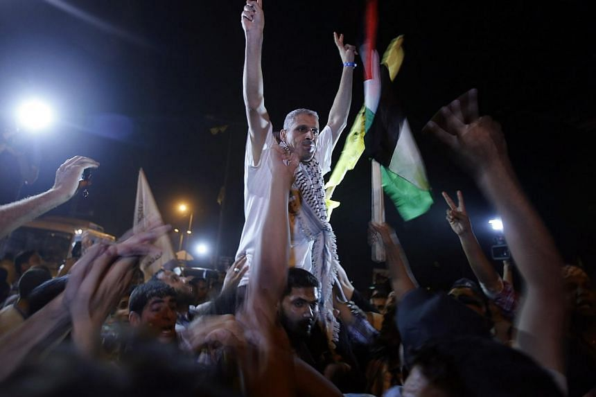 A freed Palestinian prisoner gestures upon his arrival near Erez crossing, between Israel and northern Gaza Strip, early Aug 14, 2013. Israel began an operation to free 26 Palestian prisoners on Tuesday hours before the two sides were to hold ne
