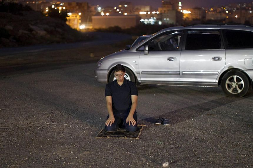 A Palestinian from the Israeli occupied West Bank prays as he waits close to the Israeli military prison of Ofer, in the village of Betunia, for the release of Palestinian prisoners on Aug 13, 2013. Israel began an operation to free 26 Palestian pris