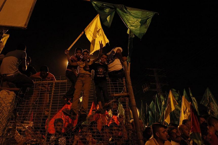 Palestinians celebrate and wave green Hamas and yellow Fatah flags as they wait for the released prisoners at a checkpoint at the entrance of Beit Hanoun between north of Gaza Strip and Israel, Tuesday, Aug 13, 2013. Irael began an operation to free