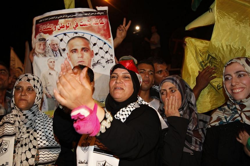 Palestinian relatives of Atif Shaat, celebrate while waiting for his release at the checkpoint at the entrance of Beit Hanoun between north of Gaza Strip and Israel, Tuesday, Aug 13, 2013. Israel began an operation to free 26 Palestian prisoners on T