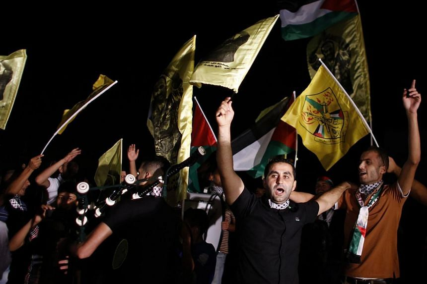 Palestinians wave flags and shout as they await the release of prisoners outside the Israeli prison of Ofer, near the West Bank city of Ramallah, Aug 13, 2013.Israel began an operation to free 26 Palestian prisoners on Tuesday hours before the