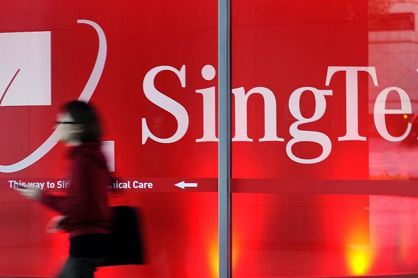 A woman walks past signage for Singapore Telecommunications Ltd. (SingTel) at a retail outlet in Singapore on May 13, 2013. SingTel's 4G mobile users will end up paying twice as much for their excess data charges from next month. -- FILE PHOTO: BLOOM