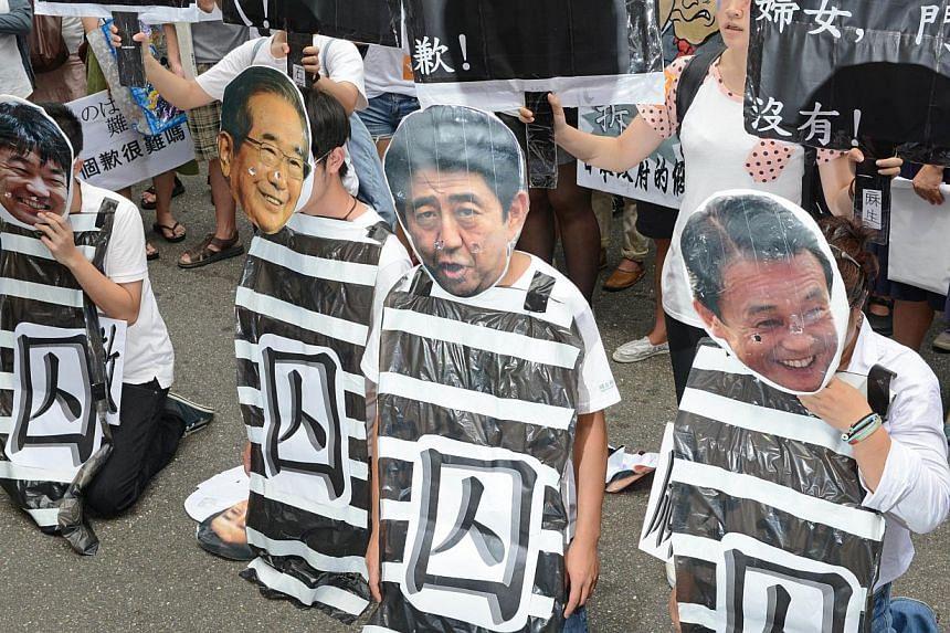 Protesters wear masks of Osaka Mayor Toru Hashimoto (left), former Tokyo governor Shintaro Ishihara (second left), Japanese Prime Minister Shinzo Abe (second right) and Foreign Minister Taro Aso (right) during a rally to demand an apology from Japan