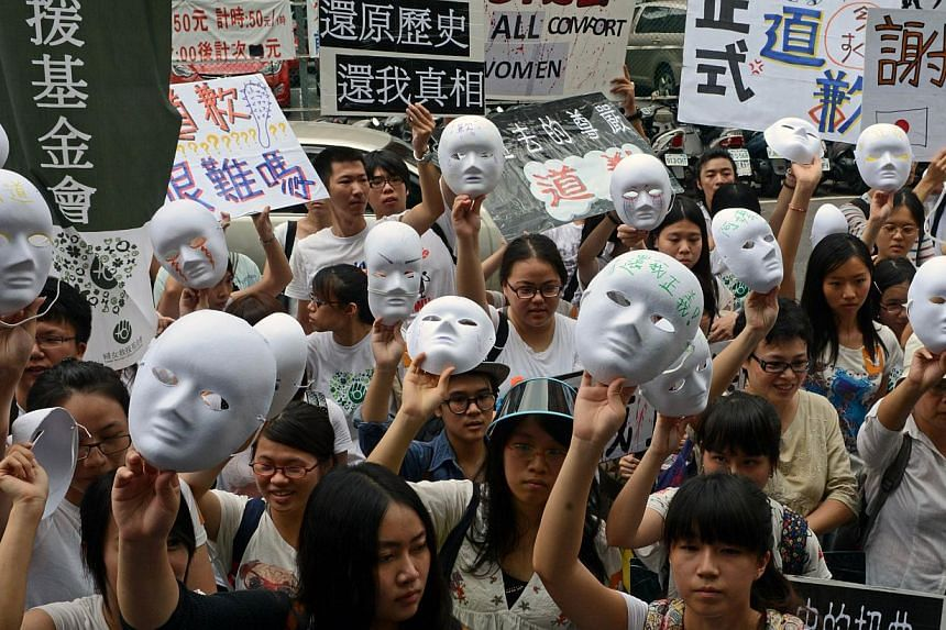 Supporters display masks as they demand an apology from Japan over the comfort women issue during a demonstration in front the Japan Interchange Association in Taipei on Wednesday, Aug 14, 2013.Around 200 Taiwanese activists protested outside J