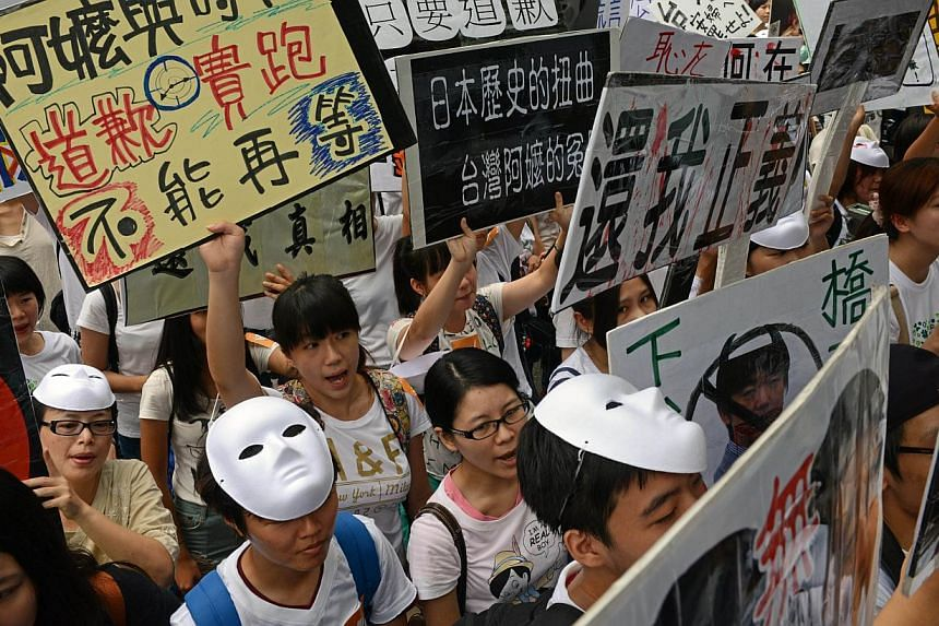 Supporters display various placards as they demand an apology from Japan over the comfort women issue during a demonstration in front the Japan Interchange Association in Taipei on Wednesday, Aug 14, 2013.Around 200 Taiwanese activists proteste