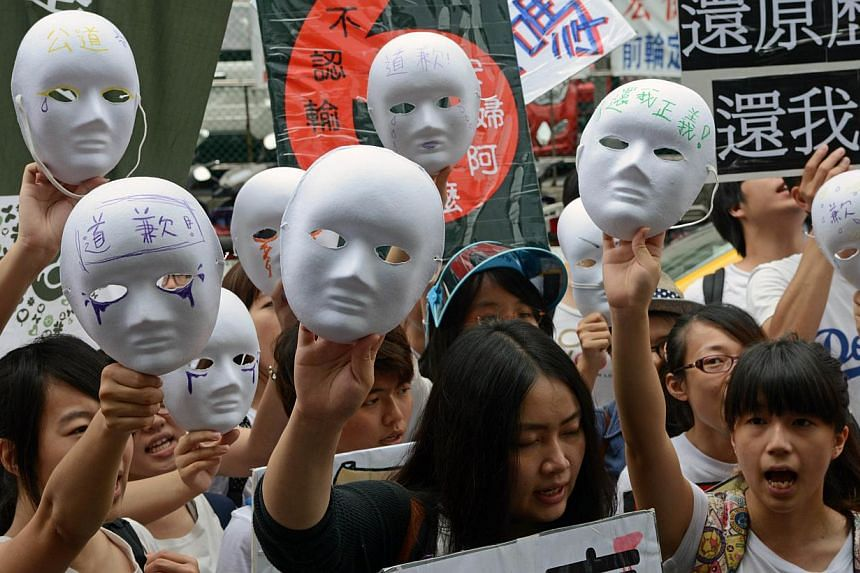 Demonstrators display masks as they demand an apology from Japan over the comfort women issue during a rally in front the Japan Interchange Association in Taipei on Wednesday, Aug 14, 2013.Around 200 Taiwanese activists protested outside Japan'