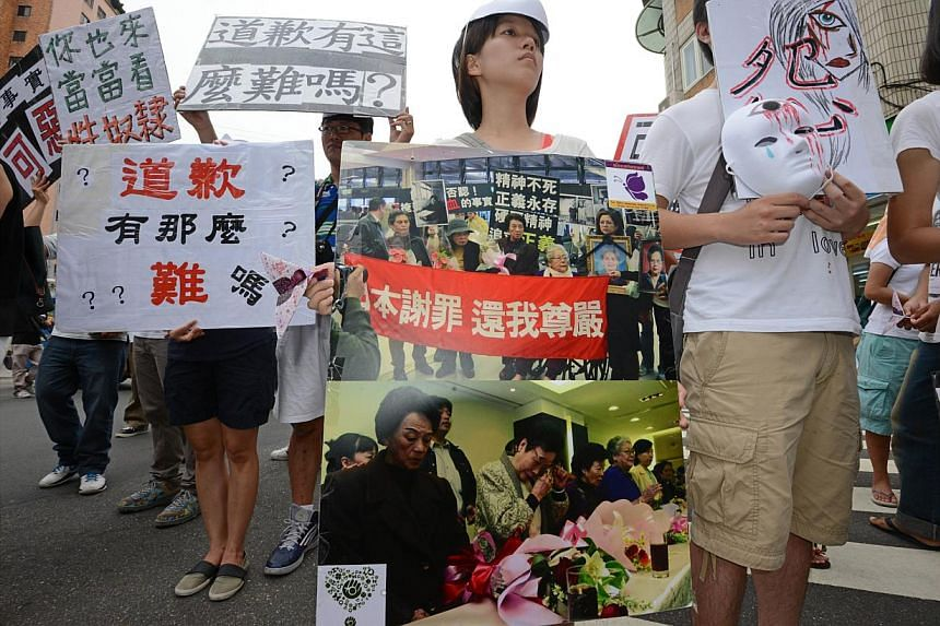 Protesters display pictures of Taiwanese comfort women during a rally to demand an apology from Japan over the comfort women issue, in front the Japan Interchange Association in Taipei on Wednesday, Aug 14, 2013.Around 200 Taiwanese activists p